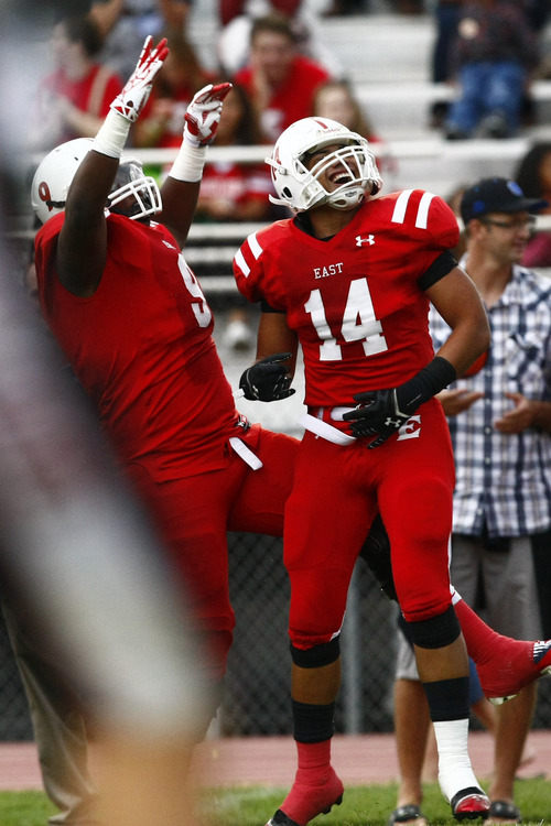 Chris Detrick  |  The Salt Lake Tribune East's Korey Rush (9) and East's Tualagi Laupata (14) after Laupata scored a touchdown during the game at East High School Friday August 23, 2013. East is winning the game 21-10 at halftime.