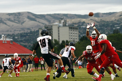 Chris Detrick  |  The Salt Lake Tribune Alta's Chipper Lucero (19) passes over East's Christian Folau (31) during the game at East High School Friday August 23, 2013. East is winning the game 21-10 at halftime.