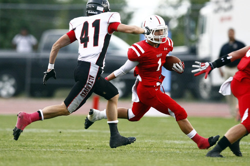 Chris Detrick  |  The Salt Lake Tribune East's Malaki Solovi (1) runs past Alta's Zack Moreton (41) during the game at East High School Friday August 23, 2013. East is winning the game 21-10 at halftime.