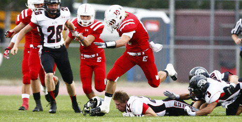 Chris Detrick  |  The Salt Lake Tribune East's Preston Curtis (10) runs over Alta's Luke Christensen (22) and Alta's Sam Llavina (3) during the game at East High School Friday August 23, 2013. East is winning the game 21-10 at halftime.