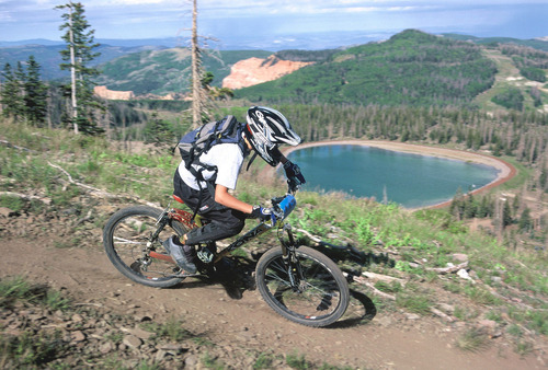 Brianheadmtnbike1 - A mountain biker zooms past a small lake while riding the trails around Brian Head. Photo by Chris Dever.