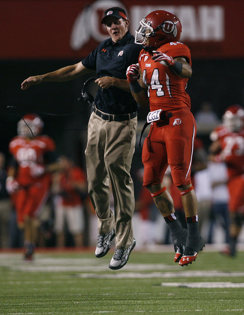 Scott Sommerdorf   |  The Salt Lake Tribune Utah special teams coach Jay Hill air-bumps with RB Lucky Radley after Utah recovered an on-side kick. Utah beat Utah State 30-26, Thursday, August 29, 2013.