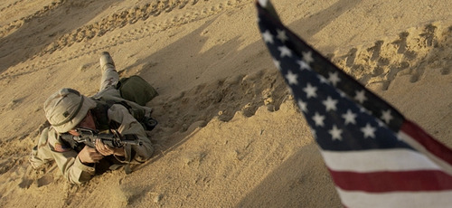 FILE - This Jan. 25, 2003 file photo shows an US soldier lying with his rifle in front of an American flag that hangs from a Humvee during live fire exercises in the Kuwaiti desert south of Iraq. Thousands of troops are assembling in Kuwait ahead of possible war with Iraq. President Barack Obama is poised to become the first U.S. leader in three decades to attack a foreign nation without broad international support or in direct defense of Americans.  Not since President Ronald Reagan ordered an invasion of the Caribbean island of Grenada in 1983 has the U.S. been so alone in pursuing major lethal military action beyond a few attacks responding to strikes or threats against its citizens.  (AP Photo/Laura Rauch, File)