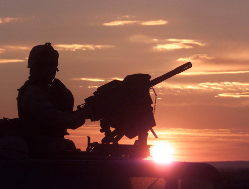 FILE This Nov. 14, 2002 file-pool photo shows a US soldier, a members of the 82nd Airborne Division, securing an area from the top of an armored vehicle on the sunset near the town of Yayeh Kehl, Paktia province, Afghanistan. President Barack Obama is poised to become the first U.S. leader in three decades to attack a foreign nation without broad international support or in direct defense of Americans. Not since President Ronald Reagan ordered an invasion of the Caribbean island of Grenada in 1983 has the U.S. been so alone in pursuing major lethal military action beyond a few attacks responding to strikes or threats against its citizens.  (AP Photo/Amel Emric, POOL)