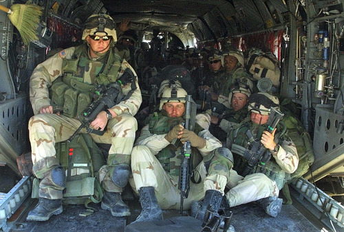 FILE - This March 13, 2002 file photo shows US Troops from 10th Mountain Division sitting in a Chinook helicopter on their way to take up the fight in eastern Afghanistan. President Barack Obama is poised to become the first U.S. leader in three decades to attack a foreign nation without broad international support or in direct defense of Americans.  Not since President Ronald Reagan ordered an invasion of the Caribbean island of Grenada in 1983 has the U.S. been so alone in pursuing major lethal military action beyond a few attacks responding to strikes or threats against its citizens.  (AP Photo/Mikhail Metzel, File)