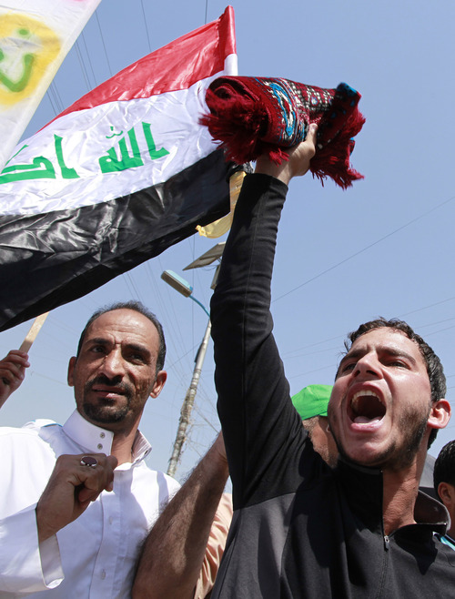 Followers of Shiite cleric Muqtada al-Sadr chant slogans against the U.S. and wave Iraqi and Syrian flags during a demonstration in Sadr City in Baghdad, Iraq, Friday, Aug. 30, 2013. Followers of Shiite cleric Muqtada al-Sadr held rallies in Baghdad and the southern Iraqi city of Basra to denounce any Western strikes against Syria. (AP Photo/Hadi Mizban)