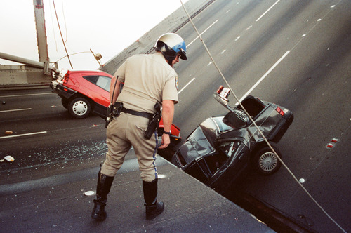 File  |  The Associated Press A California Highway Patrol officer checks the damage to cars that fell when the upper deck of the Bay Bridge collapsed onto the lower deck after the Loma Prieta earthquake in San Francisco in October 1989. Crowded roadways and packed buses, trains and ferries were on tap for commuters starting Wednesday night when officials shut down the San Francisco-Oakland Bay Bridge to traffic in preparation for a new $6.4 billion span opening late Monday or early Tuesday.