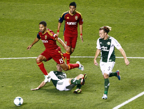 Chris Detrick  |  The Salt Lake Tribune Real Salt Lake forward Alvaro Saboru (15) runs past Portland Timbers midfielder Ben Zemanski (14) and Portland Timbers defender/midfielder Michael Harrington (5) during the first half of the game at Rio Tinto Stadium Friday August 30, 2013.