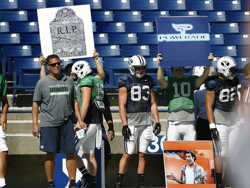 Scott Sommerdorf   |  The Salt Lake Tribune BYU OC Robert Anae, left, watches practice as his players hold up two of many boards that signal plays in to his speeded up offense during football practice at BYU, Wednesday, August 21, 2013.