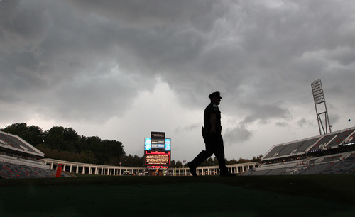 RETRANSMISSION TO CORRECT NAME OF PUBLICATION - A University of Virginia police officer patrols Scott Field after lightning from a storm caused officials to evacuate the stadium during the first half of an NCAA college football game football game, Saturday, Aug. 31, 2013 in Charlottesville, Va. (AP Photo/The Daily Progress, Andrew Shurtleff)