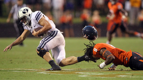 Virginia safety Anthony Harris (8) has his helmet dislodged by the foot of BYU quarterback Taysom Hill (4) during the second half of an NCAA college football game, Saturday, Aug. 31, 2013, in Charlottesville, Va. Virginia defeated BYU 19-16. (AP Photo/The Daily Progress, Andrew Shurtleff)