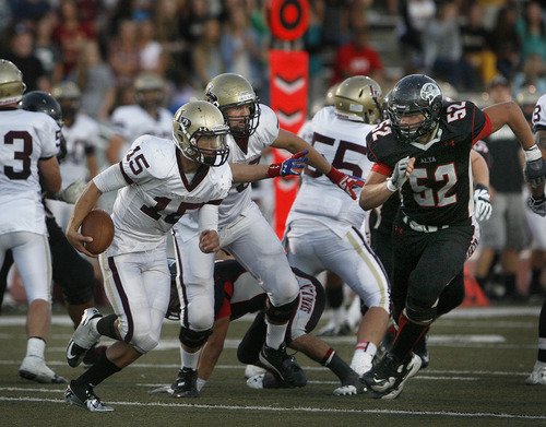 Scott Sommerdorf   |  The Salt Lake Tribune Lone Peak QB Baron Grajkowski scrambles for yardage as Alta's Nathan Richards, #52, s=zeroes in on him during first half play. Lone Peak held a 10-7 lead over Alta at the half, Friday, August 30, 2013.