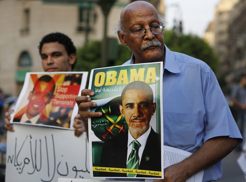 "A demonstrator holds a placard mimicking U.S. President Barack Obama during a protest against possible U.S. forces' strike in Syria, in Cairo, Egypt, Sunday, Sept. 1, 2013. The Arabic under Obama's name reads, ""Legality first,"" and ""Islamic, Islamic, Islamic, Islamic, Islamic,"" at the bottom. A top Syrian government official on Sunday dismissed the Obama administration as confused and hesitant, even as Secretary of State John Kerry said Washington has evidence of sarin gas use by Syria and that the case for a military attack is getting ""stronger and stronger."" (AP Photo/Lefteris Pitarakis)"