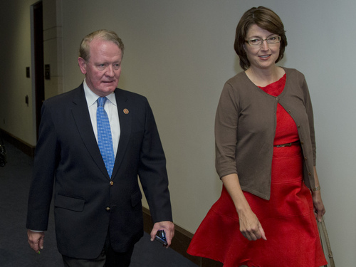 Rep. Cathy McMorris-Rodgers, R-Wash., right, and Rep. Leonard Lance, R-N.J., head to a classified members-only briefing on Syria by senior administration officials on Capitol Hill, Sunday, Sept. 1, 2013, in Washington. Sunday the Obama administration confidently predicted congressional backing for limited action in Syria. Further classified meetings are scheduled in upcoming days.  (AP Photo/Carolyn Kaster)