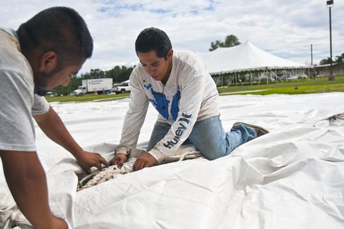 Chris Detrick     The Salt Lake Tribune Diamond Rental's Oscar Bernardino, right, and Erik Gallardo work at setting up tents at Magna Park Sunday September 1, 2013.