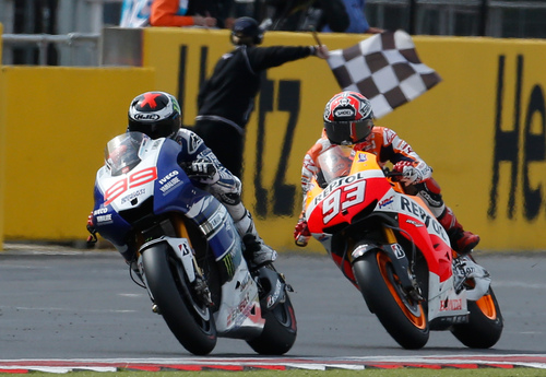 Jorge Lorenzo of Spain, left, crosse the finish line ahead of countryman Marc Marquez to win the MotoGP race of the British Grand Prix at the Silverstone circuit in Silverstone, England, Sunday, Sept. 1, 2013. Redding won the race, Nakagami was second and Luthi third. (AP Photo/Matt Dunham)