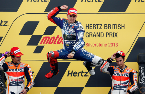 Jorge Lorenzo of Spain jumps on the podium after winning the MotoGP race of the British Grand Prix at the Silverstone circuit in Silverstone, England, Sunday, Sept. 1, 2013.  At left is Marc Marquez, who finished second, and at right Dani Pedrosa who was third. (AP Photo/Matt Dunham)