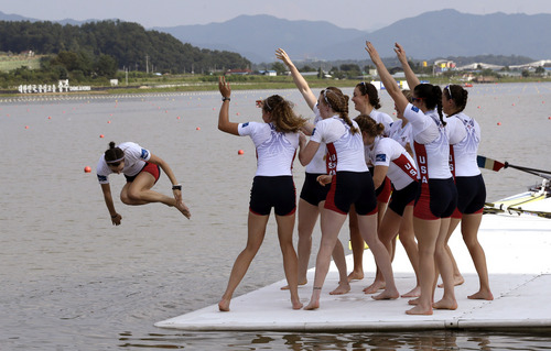U.S. rowers throw Katelin Snyder, left, into the water in the celebration of their win in the women's eight final of the World Rowing Championships in Chungju, south of Seoul, South Korea, Sunday, Sept. 1, 2013. (AP Photo/Lee Jin-man)