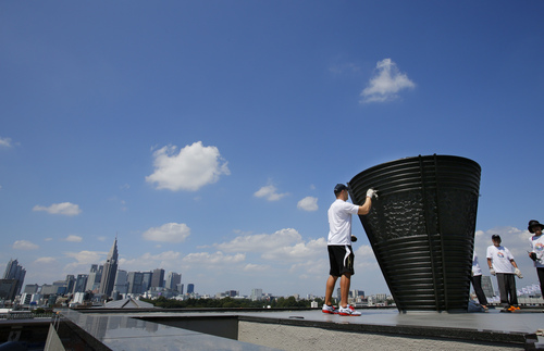 Former Olympic hammer throw champion Koji Murofushi of Japan, center, cleans the Olympic cauldron, which was used at the 1964 Tokyo Olympics, with a group of children during an event promoting Tokyo as the host city for the 2020 Olympics at the national stadium in Tokyo, Sunday, Sept. 1, 2013.  (AP Photo/Shizuo Kambayashi)