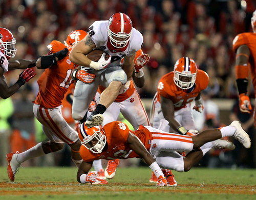 Georgia tight end Arthur Lynch (88) jumps over the tackle of Clemson safety Korrin Wiggins (12) after a catch in the second half of their NCAA college football game at Memorial Stadium, Saturday, Aug. 31, 2013, in Clemson, S.C. Clemson defeated Georgia 38-35. (AP Photo/Atlanta Journal-Constitution, Jason Getz)  MARIETTA DAILY OUT; GWINNETT DAILY POST OUT; LOCAL TV OUT; WXIA-TV OUT; WGCL-TV OUT.