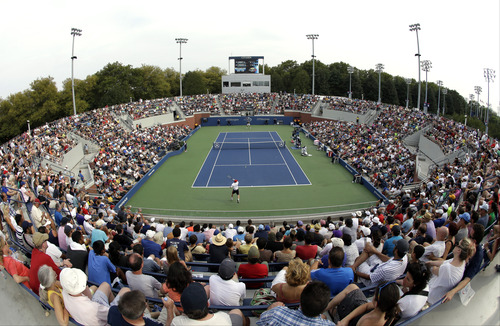 In this photograph taken with a fisheye lens, tennis fans watch a match between Richard Gasquet, of France, and Dmitry Tursunov, of Russia, during the third round of the 2013 U.S. Open tennis tournament, Saturday, Aug. 31, 2013, in New York. (AP Photo/Julio Cortez)