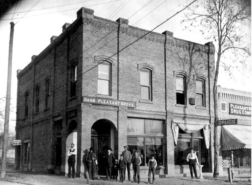 Men and boys stand outside the Pleasant Grove Bank, a dentist office at the rear. The Pleasant Grove Drug Company is just out of the frame at right.