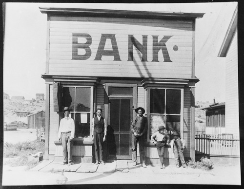 Bank at Milford, Utah. It was the banking center for Frisco and Newhouse at the time the old Horn silver mine was at top production. The man in the center is Chesley Barton, cashier.