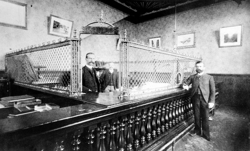 Two men stand in the interior of the American Bank of Salt Lake City which was incorporated in 1890. It was the successor to the Bank of Salt Lake City and located at 232 S. Main St. During that time period, patrons simply had to scrawl a note on a piece of paper and banks would honor the draft. Checks were considered extravagant.