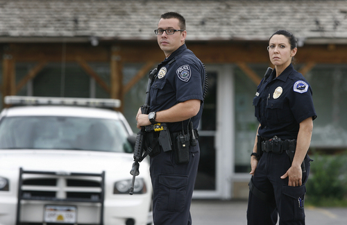 Scott Sommerdorf   |  The Salt Lake Tribune South Jordan police officers stand at a roadblock at the intersection of 12400 Souh, and Fort Street in Draper on Sunday, September 1, 2013.  Draper police Sgt. Derek Johnson was shot and killed just south of there.