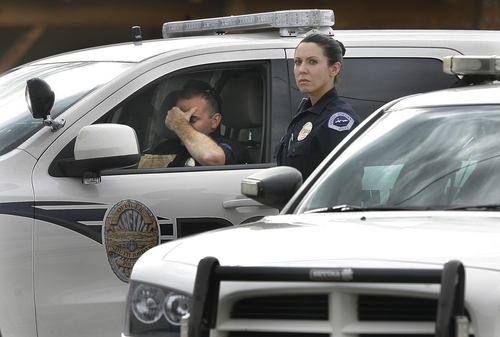 Two South Jordan police officers pause while talking near a roadblock at the intersection of 12400 South, and Fort Street in Draper, Sunday, Sept. 1, 2013. A Draper police officer was shot and killed just south of there. (AP Photo/The Salt Lake Tribune, Scott Sommerdorf)