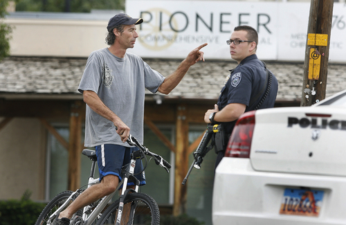 A man asks a South Jordan police officer if he can be allowed to pass through a roadblock in order to go to his home inside the cordoned-off area police are guarding south of the intersection of 12400 South, and Fort Street in Draper, Sunday, Sept. 1, 2013. He was turned away. A Draper police officer was shot and killed just south of there.  (AP Photo/The Salt Lake Tribune, Scott Sommerdorf)