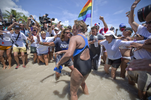 United States endurance swimmer Diana Nyad is greeted by a crowd as she walks on to the Key West, Fla., shore Monday, Sept. 2, 2013, becoming the first person to swim from Cuba to Florida without the help of a shark cage. Nyad arrived at the beach just before 2 p.m. EDT, about 53 hours after she began her swim in Havana on Saturday. (AP Photo/J Pat Carter)