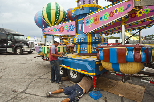 Chris Detrick  |  The Salt Lake Tribune Maximino Cortes, left, and Celerino Mendoza work at setting up the ride 'Up and Away' before the start of the Utah State Fair Tuesday September 3, 2013. The Utah State Fair begins on Thursday, when the 2013 fair opens its 11-day run at the Fairpark at 266 N. 1000 West. The fair has been held at this Salt Lake City location since 1902.
