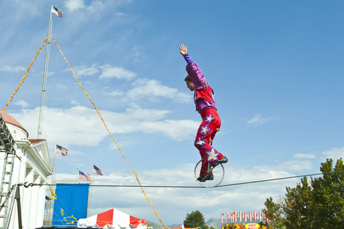 Chris Detrick  |  The Salt Lake Tribune Cirque Equinox's Fletcher Runyan, 28, rides a unicycle on a tight wire at the Utah State Fair Thursday September 6, 2012.