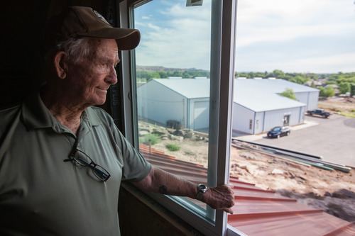 Trevor Christensen     Special to the Tribune  During a tour of Adelante Village, a women's shelter currently under construction by the Erin Kimball Memorial Foundation, Co-Founder of the organization Don Kimball looks out an apartment window as Dixie Gun Worx can be seen in the background on Wednesday, August 21, 2013. Dixie GunWorx is a firearms and gunsmithing shop looking to put in a firing range near the shelter.