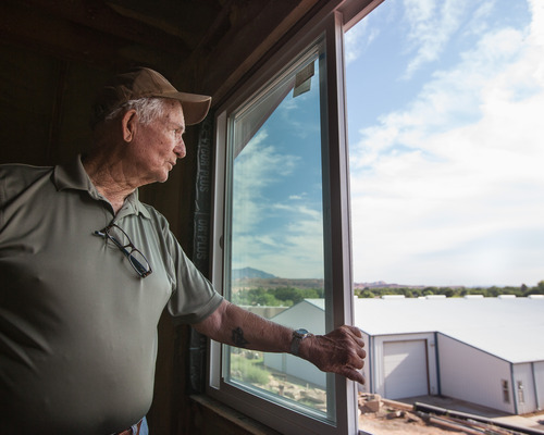 Trevor Christensen     Special to the Tribune  During a tour of Adelante Village, a women's shelter currently under construction by the Erin Kimball Memorial Foundation, Co-Founder of the organization Don Kimball looks out an apartment window at Dixie Gun Worx on Wednesday, August 21, 2013. Dixie GunWorx is a firearms and gunsmithing shop looking to put in a firing range near the shelter.