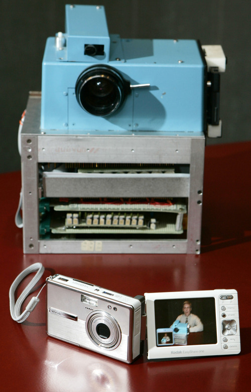 Associated Press file photo Kodak's revenue has tumbled because of slowing demand for traditional film and competition in digital cameras. Its protoyype digital camera, built in 1975, is shown next to Kodak's models.