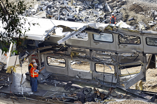 File - This Sept. 14, 2008 file photo shows investigators photographing the mangled inside of a Metrolink  commuter train in Chatsworth, Calif. Despite a rash of deadly train crashes, the railroad industry's allies in Congress are trying to push back the deadline for installing technology to prevent the most catastrophic types of collisions to at least 2020, half a century after accident investigators first called for such safety measures.  (AP Photo/Richard Vogel, File)
