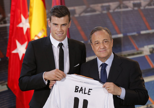 Welsh international soccer player Gareth Bale and Real Madrid President Florentino Perez pose during his official presentation at the Santiago Bernabeu stadium  in Madrid, Spain, Monday, Sept. 2, 2013 after signing for Real Madrid. The Spanish club announced Sunday that Bale has signed a six-year contract, and a person familiar with the deal said the fee was a world-record euro100 million ($132 million).  (AP Photo/Daniel Ochoa de Olza)