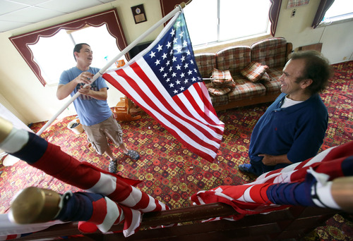 Francisco Kjolseth     The Salt Lake Tribune DeVaughn Simper, left, a father of three young children who was laid off earlier this year and out of work for awhile shows off some of the flags he uses to teach protocol about their handling to Steven Roe who is renting his basement in Taylorsville to supplement their income. Roe a paralegal who hit hard times and had just been approved for section 8 housing has exposed some systemic problems with DWS by speaking out.