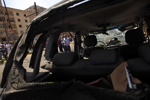 """Egyptian security personnel stand guard near the remain of a destroyed car at the scene of a bomb attack targeting the convoy of Egypt's Interior Minister Mohammed Ibrahim, in Nasr City, Cairo, Egypt, Thursday, Sept. 5, 2013. A """"large"""" explosive targeted the convoy of Egypt's interior minister Thursday in Cairo's eastern Nasr City district, the first attack on a senior government official since a coup toppled the country's Islamist president two months ago. (AP Photo/Khalil Hamra)"""
