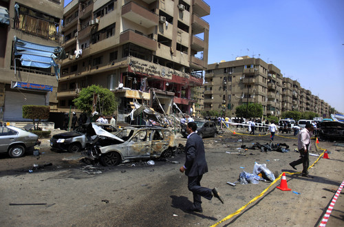 Egyptian security officers gather at the scene of a bomb attack targeting the convoy of Egypt's Interior Minister Mohammed Ibrahim, in Nasr City, Cairo, Egypt, Thursday, Sept. 5, 2013. Egypt's unrest has taken a new turn today, when a senior government official was the target of a bomb attack. (AP Photo/Khalil Hamra)