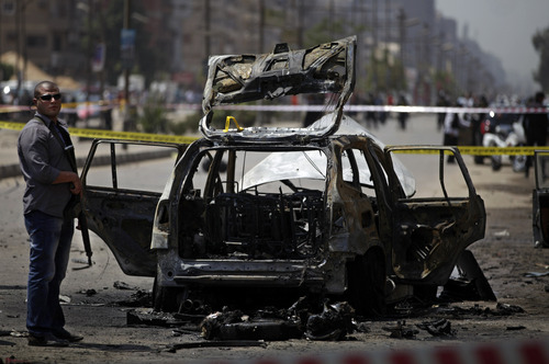 """Egyptian security personnel gather at the scene of a bomb attack targeting the convoy of Egypt's Interior Minister Mohammed Ibrahim, in Nasr City, Cairo, Egypt, Thursday, Sept. 5, 2013. A """"large"""" explosive targeted the convoy of Egypt's interior minister Thursday in Cairo's eastern Nasr City district, the first attack on a senior government official since a coup toppled the country's Islamist president July 3, 2013. (AP Photo/Khalil Hamra)"""