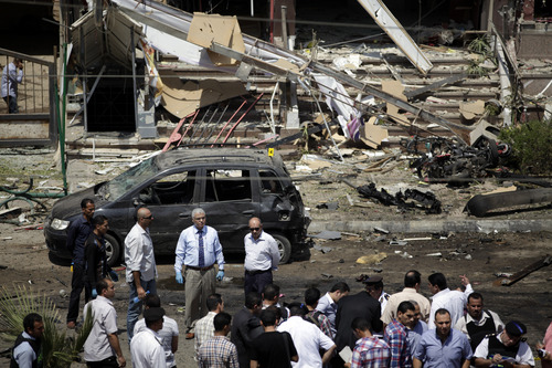 """Egyptian security personnel gather at the scene of a bomb attack targeting the convoy of Egypt's Interior Minister Mohammed Ibrahim, in Nasr City, Cairo, Egypt, Thursday, Sept. 5, 2013. A """"large"""" explosive targeted the convoy of Egypt's interior minister Thursday, the first attack on a senior government official since a coup toppled the country's Islamist president July 3, 2013. (AP Photo/Khalil Hamra)"""