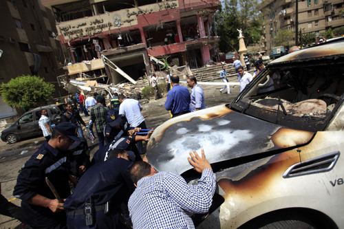 Egyptian security officers check a damaged car that was hit by a bomb attack targeting the convoy of Egypt's Interior Minister Mohammed Ibrahim, in Nasr City, Cairo, Egypt, Thursday, Sept. 5, 2013. Egypt's unrest has taken a new turn today, when a senior government official was the target of a bomb attack. (AP Photo/Khalil Hamra)