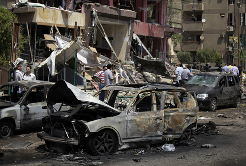 """Egyptian security personnel investigate the scene of a bomb attack targeting the convoy of Egypt's Interior Minister Mohammed Ibrahim, in Nasr City, Cairo, Egypt, Thursday, Sept. 5, 2013. A """"large"""" explosive targeted the convoy of Egypt's interior minister Thursday in Cairo's eastern Nasr City district, the first attack on a senior government official since a coup toppled the country's Islamist president July 3, 2013. (AP Photo/Khalil Hamra)"""