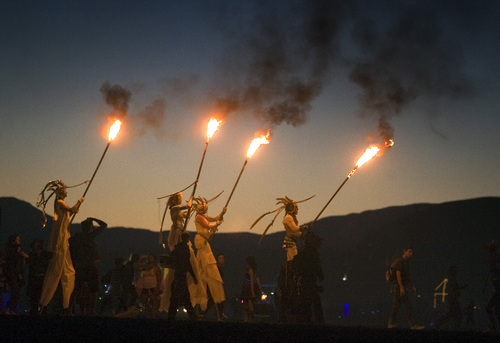 Rick Egan  | The Salt Lake Tribune   Torch bearers on stilts lead the procession to the Burning Man, Saturday, August 31, 2013.