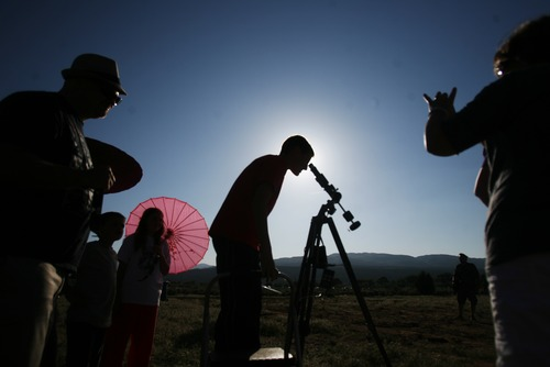 Kim Raff | The Salt Lake Tribune Jake Rehkop looks through a telescope as people view the annular solar eclipse in Kanarraville, Utah on May 20, 2012. Kim Raff | The Salt Lake Tribune