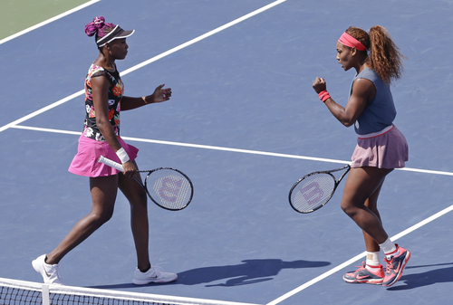 Venus Williams, left, and Serena Williams react after a point against Sara Errani, of Italy, and Roberta Vinci, of Italy, during the women's doubles quarterfinals of the 2013 U.S. Open tennis tournament, Thursday, Sept. 5, 2013, in New York. (AP Photo/Mike Groll)
