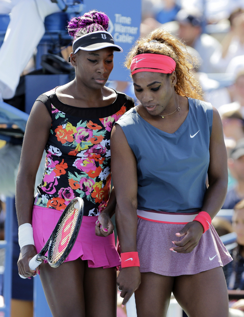 Venus Williams, left, and Serena Williams plan the next point against Sara Errani, of Italy, and Roberta Vinci, of Italy, during the women's doubles quarterfinals of the 2013 U.S. Open tennis tournament, Thursday, Sept. 5, 2013, in New York. (AP Photo/Mike Groll)